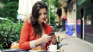 Woman on smartphone eating lunch